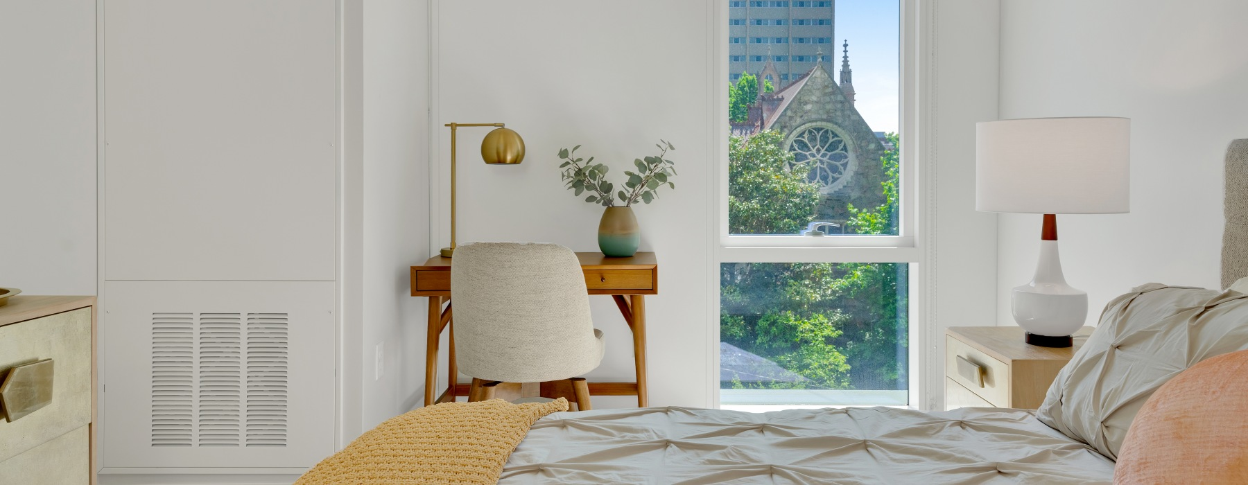 bedroom with natural lighting through high window and city views